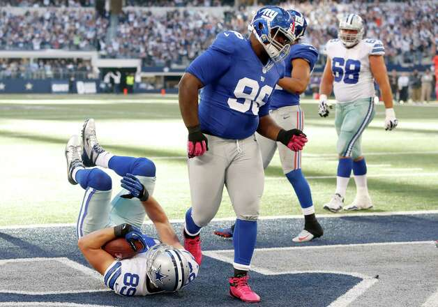 Dallas Cowboys tight end John Phillips (89) scores a touchdown as New York Giants defensive tackle Marvin Austin steps away during the second half of an NFL football game Sunday, Oct. 28, 2012 in Arlington, Texas. (AP Photo/Sharon Ellman) Photo: Sharon Ellman, Associated Press / FR170032 AP