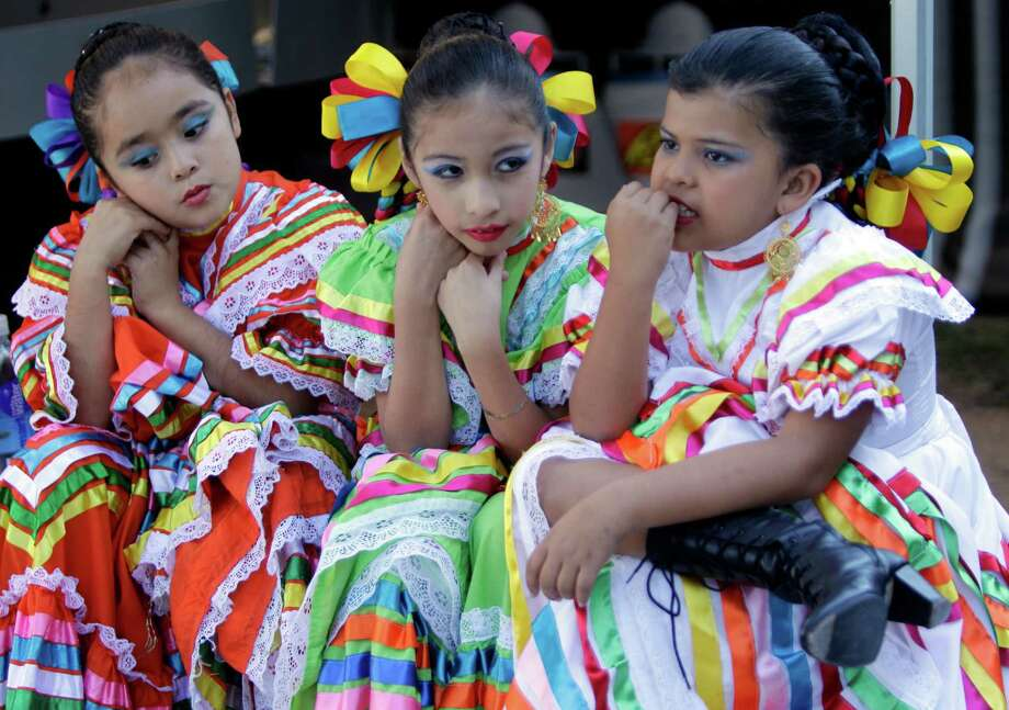 MECA Ballet Folklorico members Jezzy Rodirguez, 8, left, Sofia Rodirguez, 10, center, and Karen Castro, 8, right, wait to go on stage for performance during the Día de los Muertos Festival at MECA, Multicultural Education And Counseling through the Arts, 1900 Kane Street, Sunday, Oct. 28, 2012, in Houston. The two-day Día de los Muertos Festival is a public celebration of community folk art traditions that commemorate family and community ancestors. Festival events included community altar exhibits, foods from Latin American countries, vendors selling Day of the Dead arts and crafts, and live performances of music and dance. Photo: Melissa Phillip, Houston Chronicle / © 2012 Houston Chronicle