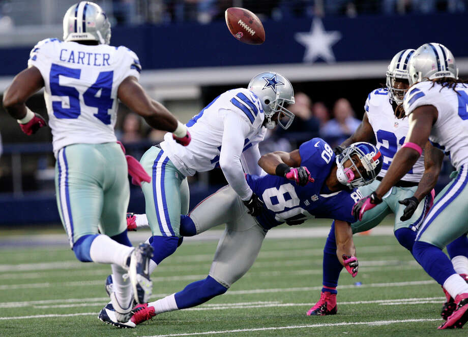 After taking a hit from Dallas Cowboys' safety Gerald Sensabaugh, center left, New York Giants' wide receiver Victor Cruz, (80), can't hold on to a pass during the second half at Cowboys Stadium in Arlington, Texas, Sunday, Oct. 28, 2012. The ball was intercepted by Danny McCray, (40), on the right. The Giants won, 29-24. Photo: Jerry Lara, Express-News / © 2012 San Antonio Express-News