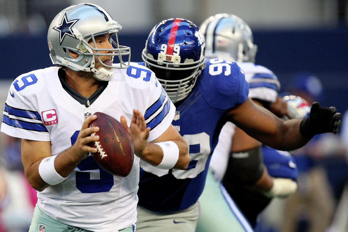 Dallas Cowboys' quarterback Tony Romo gets pressure from New York Giants' Chris Canty during the first half at Cowboys Stadium in Arlington, Texas, Sunday, Oct. 28, 2012.