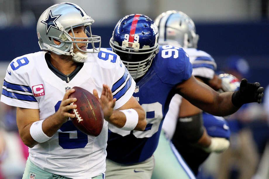 Dallas Cowboys' quarterback Tony Romo gets pressure from  New York Giants' Chris Canty during the first half at Cowboys Stadium in Arlington, Texas, Sunday, Oct. 28, 2012. Photo: Jerry Lara, Express-News / © 2012 San Antonio Express-News