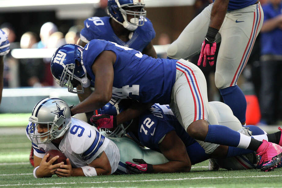 Dallas Cowboys' quarterback Tony Romo lies at the bottom of the pile after he was sacked by New York Giants' Osi Umenyiora, (72), and Mathias Kiwanuka, (94), during the first half at Cowboys Stadium in Arlington, Texas, Sunday, Oct. 28, 2012. Photo: Jerry Lara, Express-News / © 2012 San Antonio Express-News