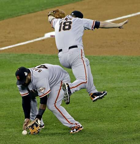 San Francisco Giants' Matt Cain (18) gets out of the way as Pablo Sandoval fields a bunt by Detroit Tigers' Quintin Berry during the third inning of Game 4 of baseball's World Series Sunday, Oct. 28, 2012, in Detroit. (AP Photo/Paul Sancya ) Photo: Paul Sancya, Associated Press