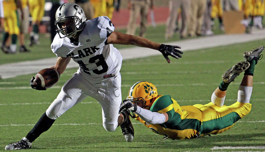 Cougar tailback Branden Valle gets away from Moses Berrones and goes on to scramble in for a touchdown as Holmes plays Clark at Gustafson Stadium on November 3, 2012. Photo: Tom Reel, San Antonio Express-News / ©2012 San Antono Express-News