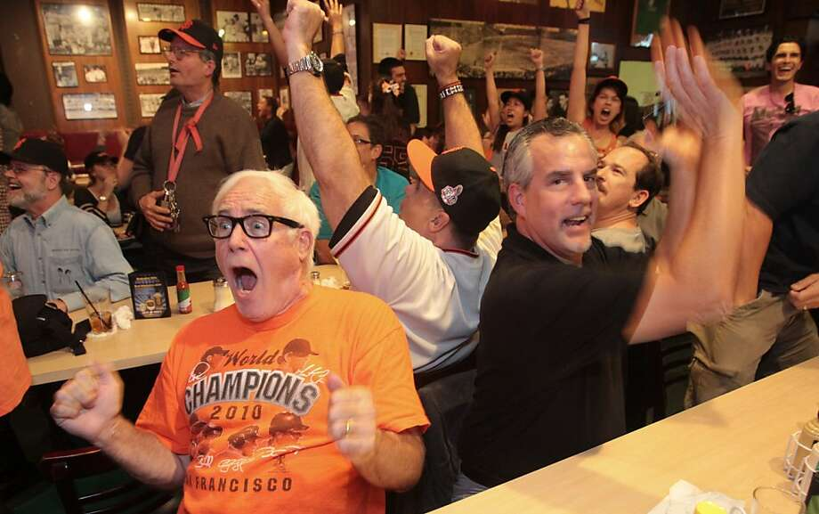 Giants fans Tim Pedersen, left,  and John Gioseffi along with others celebrate Buster Posey's two-run homer at Left O'Douls on Sunday, Oct. 28, 2012. Photo: Mathew Sumner, Special To The Chronicle