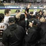 Giants' catcher Buster Posey is greeted in the dugout after hitting a 2-run homer in the 6th inning during game 4 of the World Series at Comerica Park on Sunday, Oct. 28, 2012 in Detroit, MI.