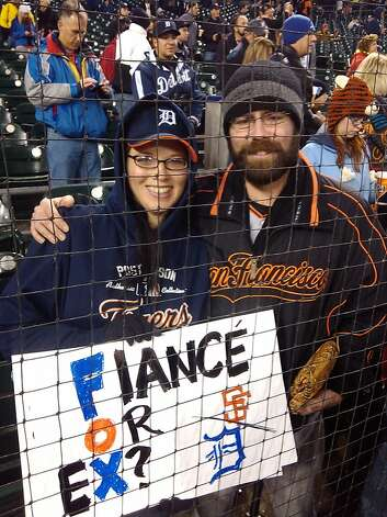 Recently engaged couple Jesse Sayers, left, a Tigers fan, and Jeremy Stokes, a Giants fan, show pride in their respective teams at Comerica Park in Detroit, MI, on Sunday, Oct. 28, 2012. Photo: Al Saracevic  Photos By MIKE DOR, San Francisco Chronicle