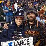 Recently engaged couple Jesse Sayers, left, a Tigers fan, and Jeremy Stokes, a Giants fan, show pride in their respective teams at Comerica Park in Detroit, MI, on Sunday, Oct. 28, 2012.