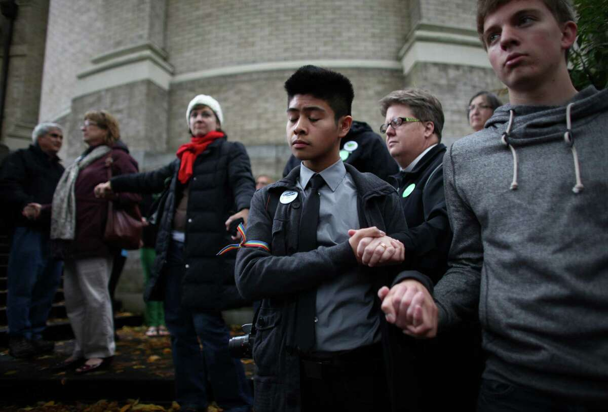 Robert Gavino, 19, prays with others as Catholics show support for marriage equality on Sunday, October 28th, 2012 on the sidewalk outside of Saint James Cathedral in Seattle. The group gathered to pray, sing and listen to speakers. The Archdiocese of Seattle, headquartered at the Cathedral, is officially opposed to Referendum 74. The stance has caused a division among some in the church.