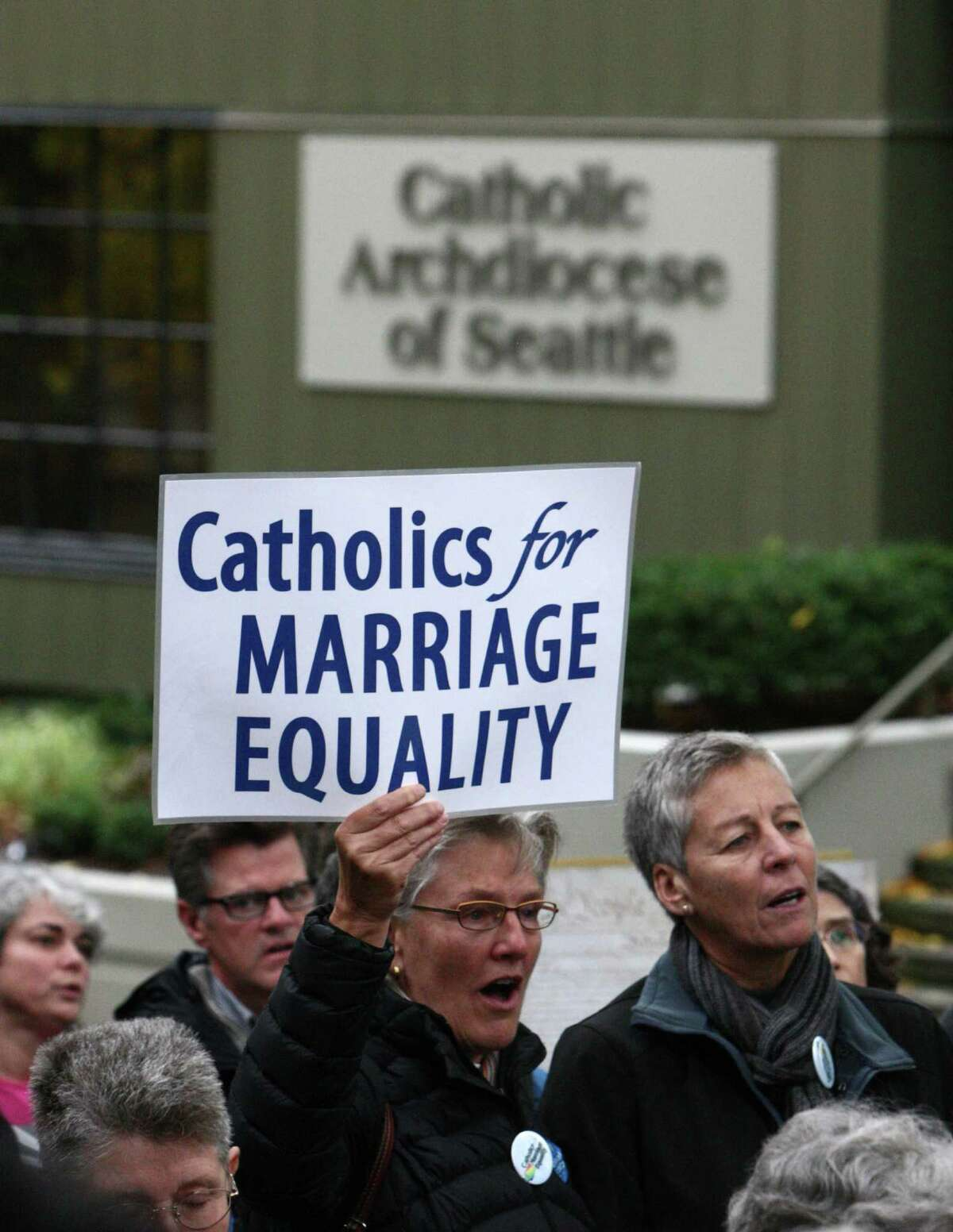 Participants sing as Catholics show support for marriage equality on Sunday, October 28th, 2012 on the sidewalk outside of Saint James Cathedral in Seattle. The group gathered to pray, sing and listen to speakers. The Archdiocese of Seattle, headquartered at the Cathedral, is officially opposed to Referendum 74. The stance has caused a division among some in the church.