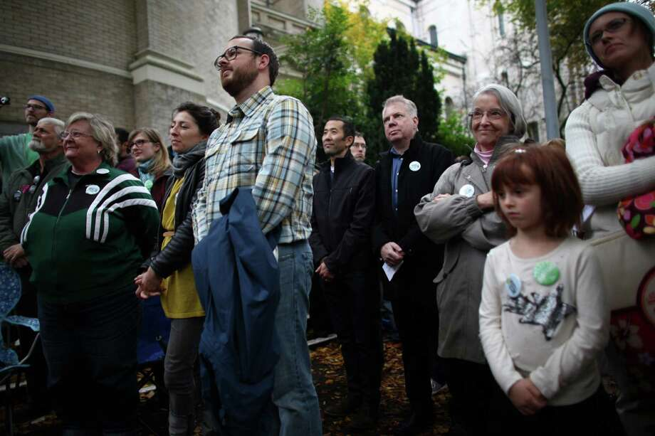 Catholics, including State Senator Ed Murray and his partner Michael Shiosaka, center, show support for marriage equality on Sunday, October 28th, 2012 on the sidewalk outside of Saint James Cathedral in Seattle. The group gathered to pray, sing and listen to speakers. The Archdiocese of Seattle, headquartered at the Cathedral, is officially opposed to Referendum 74. The stance has caused a division among some in the church. Photo: JOSHUA TRUJILLO / SEATTLEPI.COM