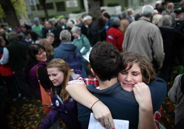 Jennifer Leard receives a hug as Catholics show support for marriage equality on Sunday, October 28th, 2012 on the sidewalk outside of Saint James Cathedral.. The Archdiocese of Seattle, headquartered at the Cathedral, is actively opposing Referendum 74. The stance has caused many Catholics to dissent. Photo: JOSHUA TRUJILLO / SEATTLEPI.COM