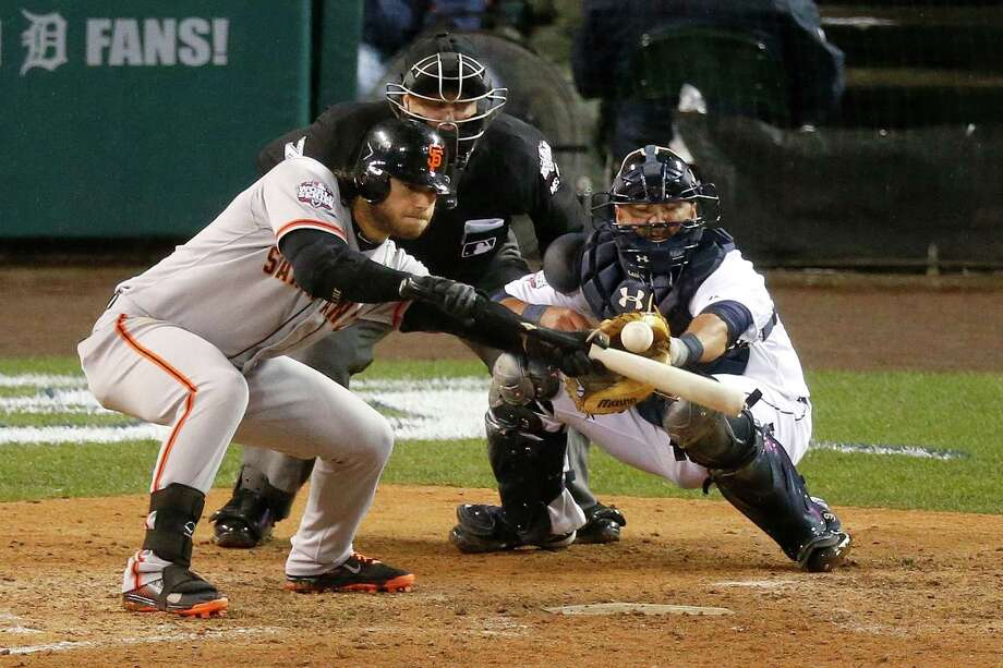 DETROIT, MI - OCTOBER 28:  Brandon Crawford #35 of the San Francisco Giants hits a sacrifice bunt against Phil Coke #40 of the Detroit Tigers in the tenth inning during Game Four of the Major League Baseball World Series at Comerica Park on October 28, 2012 in Detroit, Michigan. Photo: Leon Halip, Getty Images / Getty Images North America