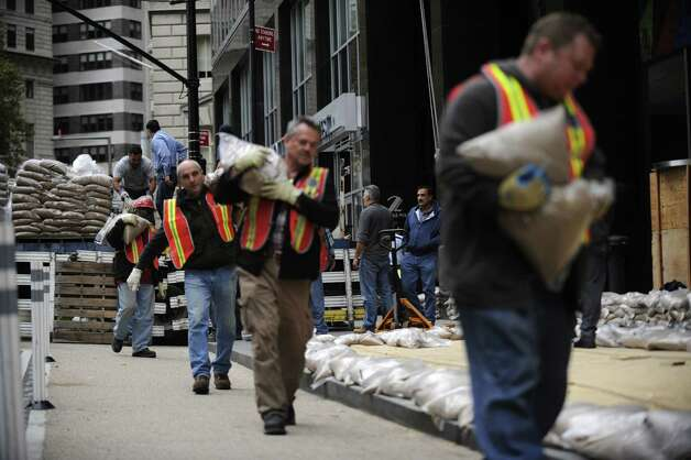 Sandbags are lined up in front of No. 2 Broadway in Battery Park in preparation of the superstorm, Sunday, Oct. 28, 2012, in New York. (AP Photo/Louis Lanzano) Photo: Louis Lanzano