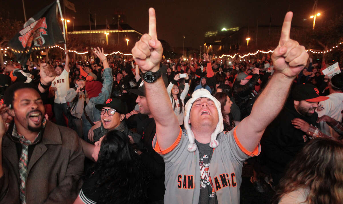 Giants fan Ronnie Gonsalvez along with others celebrate their team winning the World Series on Sunday, Oct. 28, 2012.