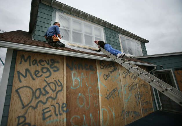 Gene Zwicharowski, left, and Mary Beth Morse cover the windows of their beach cottage with plastic sheeting in preparation for the arrival of Hurricane Sandy in the Lordship section of Stratford on Sunday, October 28, 2012. Photo: Brian A. Pounds