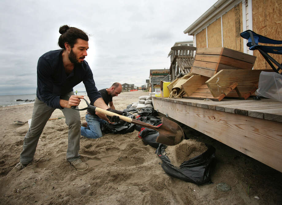 Paul Taylor, left, and Matthew Preston fill and pile sandbags in front of Preston's beachfront cottage in preparation for the arrival of Hurricane Sandy in the Lordship section of Stratford on Sunday, October 28, 2012. Photo: Brian A. Pounds