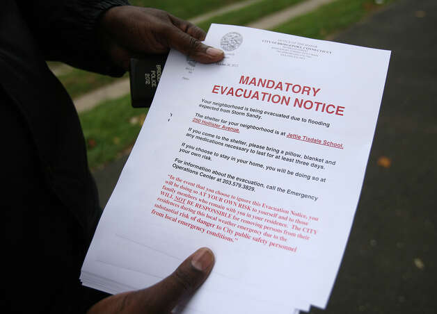 The mandatory evacuation notice being handed out the Bridgeport's East End residents in preparation for Hurricane Sandy on Sunday, October 28, 2012. Photo: Brian A. Pounds