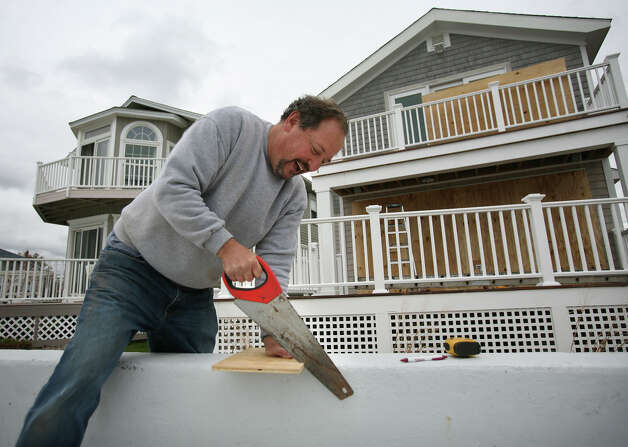 Terry Magun boards up the windows of his waterfront home in preparation for the arrival of Hurricane Sandy on Point Beach Drive in Milford on Sunday, October 28, 2012. Photo: Brian A. Pounds
