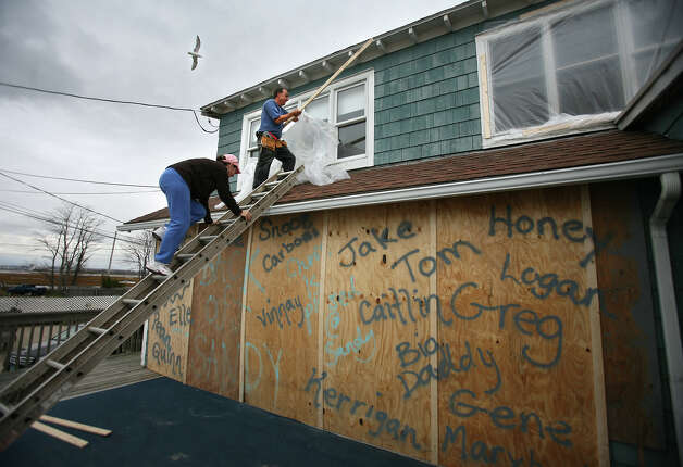 Mary Beth Morse, left, and Gene Zwicharowski cover the windows of their beach cottage with plastic sheeting in preparation for the arrival of Hurricane Sandy in the Lordship section of Stratford on Sunday, October 28, 2012. Photo: Brian A. Pounds