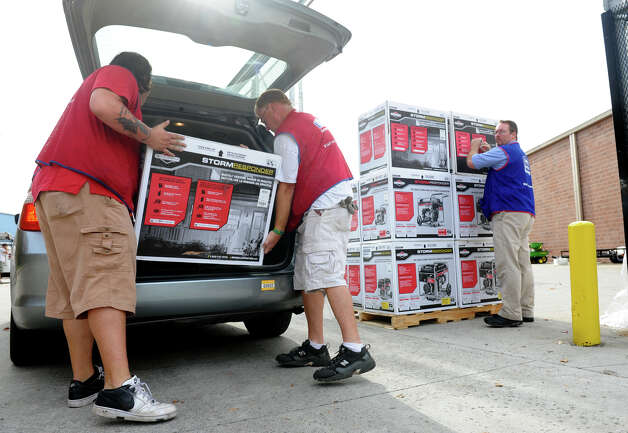Lowe's workers Chris Lund, center, and Tom Gerard, help load a generator into the back of a customer's vehicle, before the arrival of Hurricane Sandy in Milford, Conn. on Saturday October 27, 2012. Photo: Christian Abraham