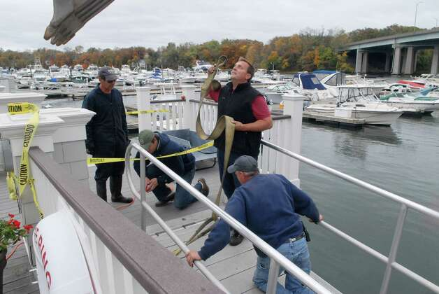 Ismael Santiago, James Hood and Terry Whaley remove the dock ramps at Beacon Point Marine in Greenwich, Conn. on Sunday October 28, 2012. in preparation for Hurricane Sandy. Photo: Dru Nadler