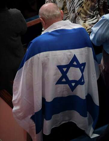 "An attendee is draped in an Israeli flag during ""A Night to Honor Israel,"" Sunday, Oct. 28, 2012, at Cornerstone Church in San Antonio. Photo: Darren Abate, Darren Abate/For The Express-New"