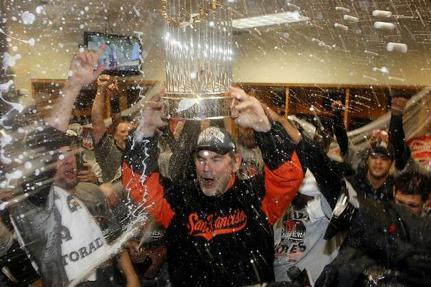 As he receives a Champagne drenching, Bruce Bochy hoists a World Series championship trophy to go with the one the Giants won in 2010. Photo: Michael Macor, The Chronicle