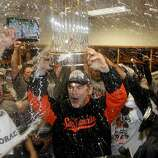 As he receives a Champagne drenching, Bruce Bochy hoists a World Series championship trophy to go with the one the Giants won in 2010.