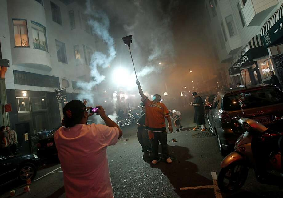 On Grant Street, smoke from fireworks and fans in the middle of the street. Giants fans in North Beach went wild as their baseball team won their second World Series title in three years Sunday October 28, 2012. Photo: Brant Ward, The Chronicle