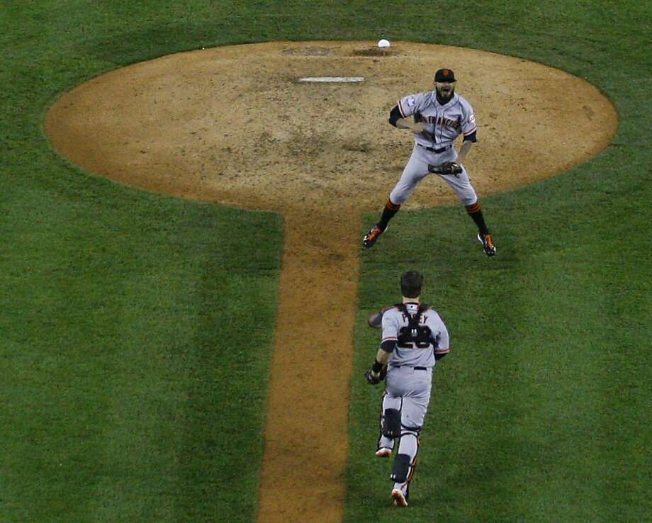 Catcher Buster Posey runs to embrace Sergio Romo after Detroit's Miguel Cabrera struck out to secure San Francisco's second title in three years. Photo: Carlos Avila Gonzalez, The Chronicle