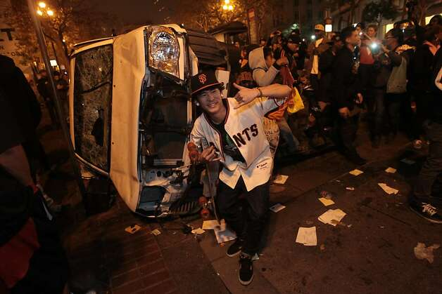 Leo Funaki stands in front of a car that was turned over on Market St. in San Francisco after the Giants won the World Series on Sunday, Oct. 28, 2012. Photo: Mathew Sumner, Special To The Chronicle / SF