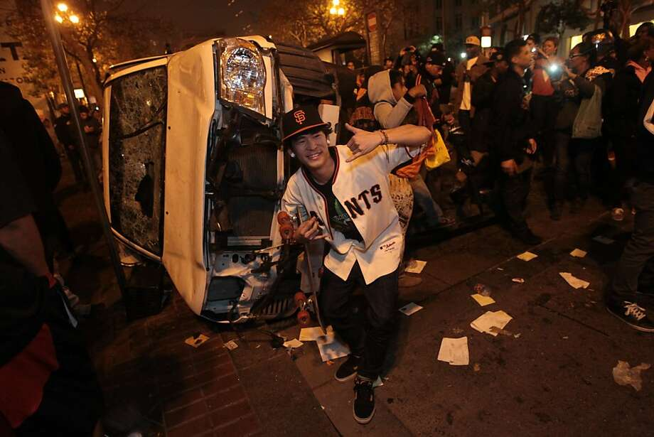 Leo Funaki stands in front of a car that was turned over on Market St. in San Francisco after the Giants won the World Series on Sunday, Oct. 28, 2012. Photo: Mathew Sumner, Special To The Chronicle