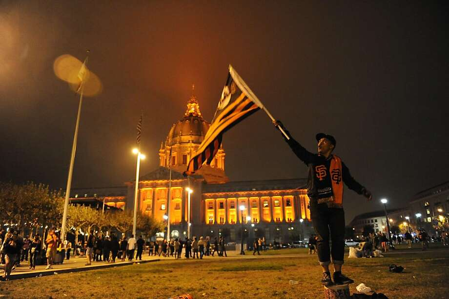 Jeremy Manongdo salutes with a flag in San Francisco after the Giants win the World Series. Photo: Susana Bates, Special To The Chronicle