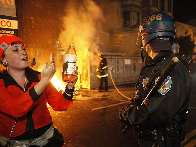 A woman attempts to provoke a Police Officer as the San Francisco Fire Department attempts to put out a fire at 24th and Mission Streets in San Francisco Calif. on Sunday, Oct. 28, 2012. The fire was set as people took to the streets to riot and celebrate the San Francisco Giants' second World Series win in three years. Photo: Alex Washburn, Special To The Chronicle