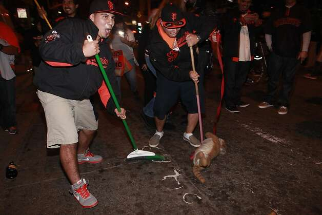 Brothers Elson and Gerardo Orantes sweep third street in front of AT&T park after the San Francisco Giants win the World Series in a four game sweep again the Detroit Tigers on Wednesday Oct. 28, 2012 in San Francisco, Calif. Photo: Mike Kepka, The Chronicle
