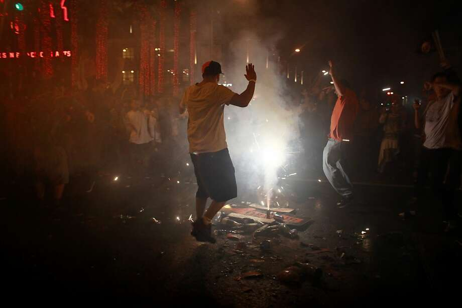 Fan dance around fireworks in the street near AT&T park after the San Francisco Giants win the World Series in a four game sweep against the Detroit Tigers on Wednesday Oct. 28, 2012 in San Francisco, Calif. Photo: Mike Kepka, The Chronicle