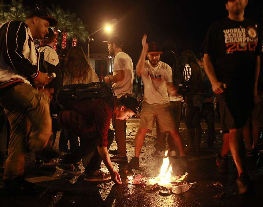 Fan dance around a small trash fire in the street near AT&T park after the San Francisco Giants win the World Series in a four game sweep against the Detroit Tigers on Wednesday Oct. 28, 2012 in San Francisco, Calif. Photo: Mike Kepka, The Chronicle