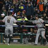 Giants' right fielder Hunter Pence is greeted by Ryan Theriot and Pablo Sandoval after scoring in the 2nd inning during game 4 of the World Series at Comerica Park on Sunday, Oct. 28, 2012 in Detroit, MI.