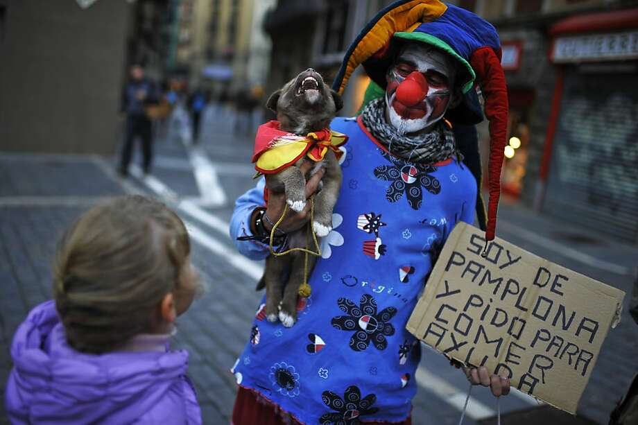 Juanjo, 32, a former Spanish Legion soldier, dressed in clown clothes, begs a coin on the street with his puppy while a girl looks at them, in Pamplona, northern Spain, Sunday, Oct. 28, 2012.  Juanjo's cardboard sign says: ''I'm of Pamplona, and begs to eat. Help''. (AP Photo/Alvaro Barrientos) Photo: Alvaro Barrientos, Associated Press