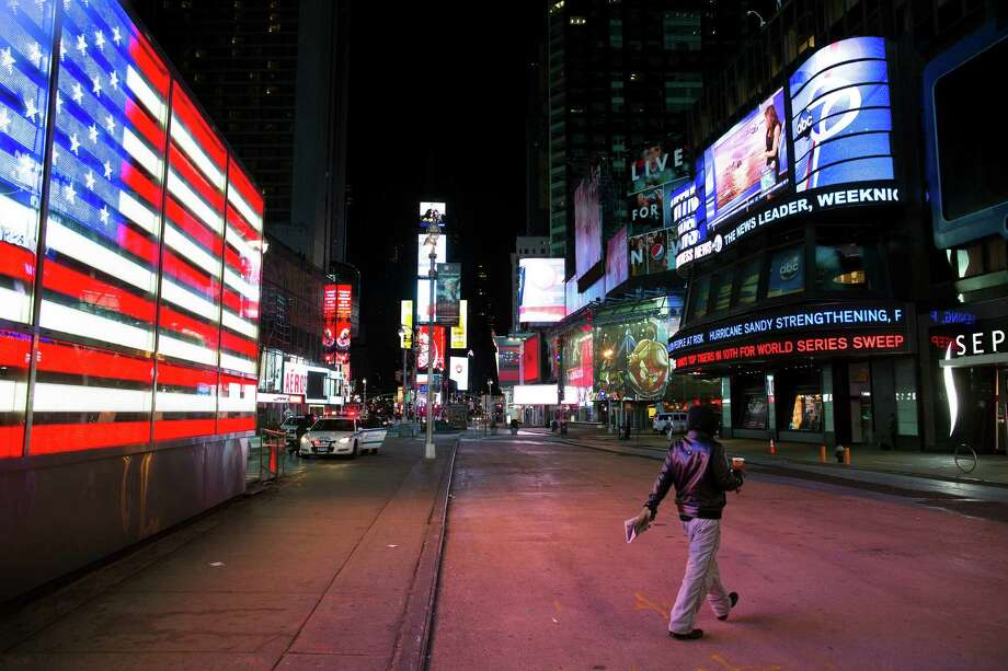 A lone pedestrian walks through an empty Times Square early, Monday, Oct. 29, 2012, in New York. Hurricane Sandy continued on its path Monday, forcing the shutdown of mass transit, schools and financial markets, sending coastal residents fleeing, and threatening a dangerous mix of high winds and soaking rain. (AP Photo/ John Minchillo) Photo: John Minchillo, Associated Press / FR170537 AP