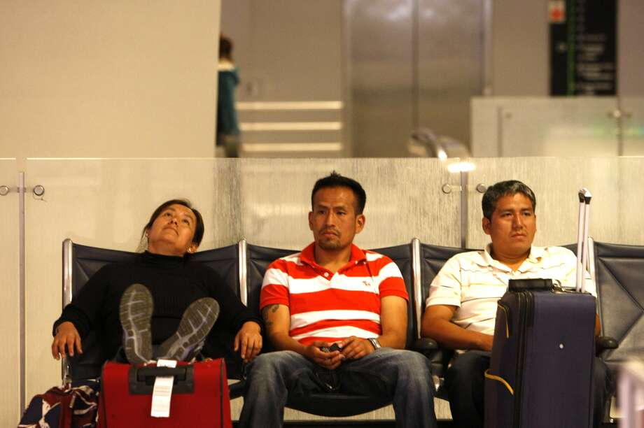 From left, Delia Reyes and her brothers, Rey and Tony Reyes, sit stranded at IAH Terminal C after finding out their flight to Washington D.C. was canceled due to Hurricane Sandy Photo: Johnny Hanson/Chronicle