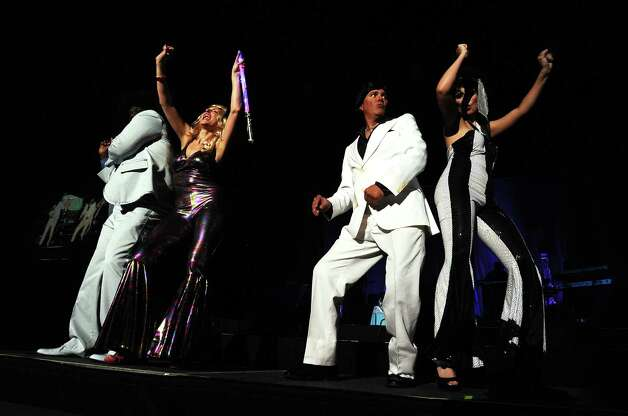 The hosts for the Putting on the Pink: Saturday Night Fever presented by the Julie Rogers Gift of Life shake their groove thing at the Beaumont Civic Center on Saturday, October 27, 2012. Photo taken: Randy Edwards/The Enterprise