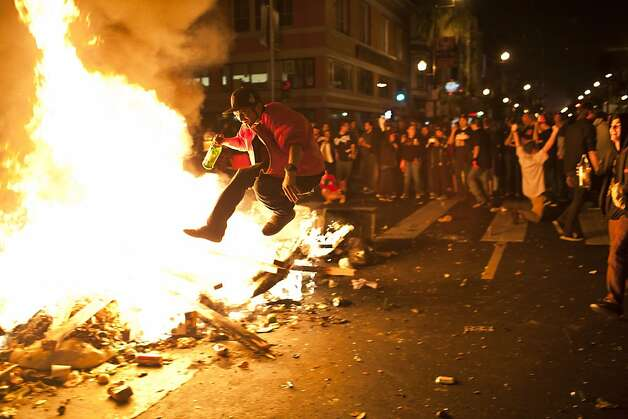 A fan celebrated by jumping over the fire during Giants World Series celebrations on Mission Street in San Francisco, Calif., Sunday, October 28, 2012. Photo: Jason Henry, Special To The Chronicle