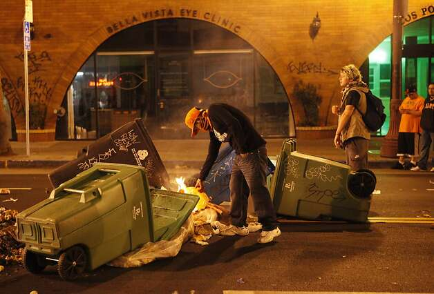 In the midst of the rioting a masked person lights trash cans on fire as Giants fans celebrate the San Francisco Giants winning their second World Series in three years in the Mission District of San Francisco Calif. on Sunday, Oct. 28, 2012. Photo: Alex Washburn, Special To The Chronicle