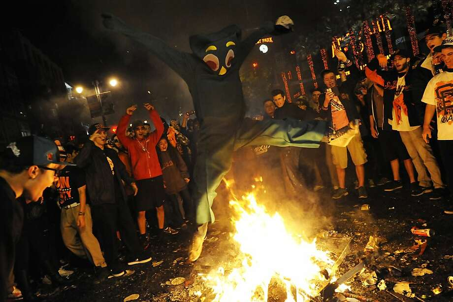 A person in a Gumby suit jumps over a fire as others cheer him on.  Fans celebrate the San Francisco Giants winning the 2012 World Series outside of AT&T park in San Francisco, Sunday October 28th, 2012. Photo: Michael Short, Special To The Chronicle