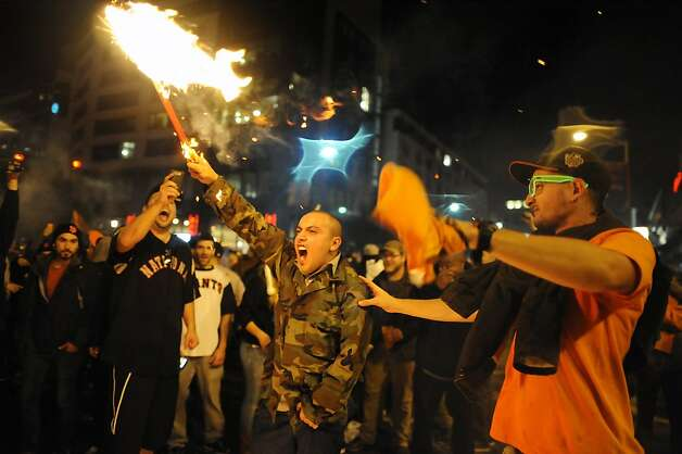 Bernardo Nabarro(center) of Pittsburg, CA holds a burning broom as he and other fans celebrate the San Francisco Giants winning the 2012 World Series outside of AT&T park in San Francisco, Sunday October 28th, 2012. Photo: Michael Short, Special To The Chronicle