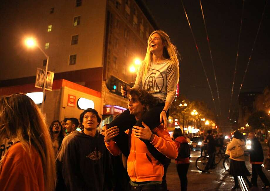 Giants fans celebrate on the corner of Market Street and 7th Avenue in downtown San Francisco following the Giants World Series win over the Detroit Tigers on Sunday October, 28. Photo: Luanne Dietz, Special To The Chronicle