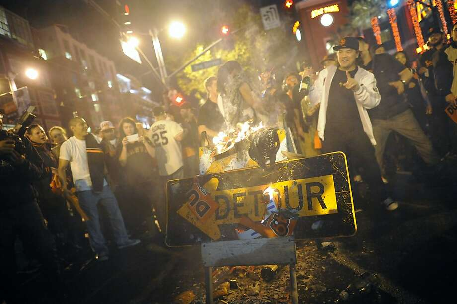 Fans light a sign on fire and dance around it as they celebrate the San Francisco Giants winning the 2012 World Series outside of AT&T park in San Francisco, Sunday October 28th, 2012. Photo: Michael Short, Special To The Chronicle