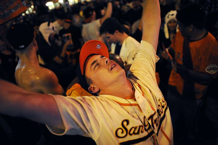 Sean Egensis of Santa Cruz throws up his arms as he and other fans celebrate the San Francisco Giants winning the 2012 World Series outside of AT&T park in San Francisco, Sunday October 28th, 2012. Photo: Michael Short, Special To The Chronicle